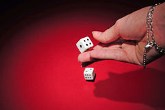 Gamble: throwing the dices. A woman had throwing two dices on a red surface. The light in the scene is spot like Royalty Free Stock Photos