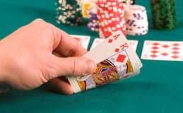The gambler. The player in poker looks the cards Stock Photos