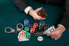 Gambler with alcohol and handcuffs Royalty Free Stock Photo