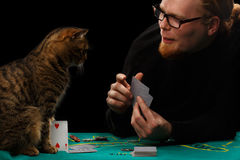 Gambler and cat. Young red-haired bearded man in glasses playing poker with tabby cat sitting at gaming table on black background Royalty Free Stock Photos