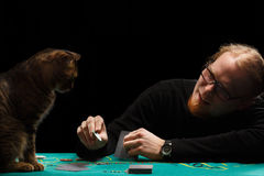 Gambler and cat. Young smiling red-haired bearded man in glasses playing poker with tabby cat sitting at gaming table on black background Royalty Free Stock Photography