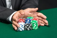 Gambler going. Poker player going all in pushing his chips forward. Symbol of addiction to the poker Royalty Free Stock Image
