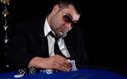 Gambler in las vegas. Poker player in black background Royalty Free Stock Photos