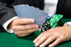 Gambler playing cards with chips on the table Stock Images