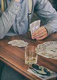 Gambler playing cards and drinking alcohol stock photo