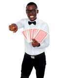 Gambler with playing cards pointing at you Royalty Free Stock Images