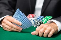 Gambler playing cards with poker chips on the table Royalty Free Stock Image