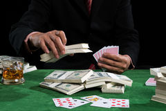 Gambler is putting bets into the piles of banknote Royalty Free Stock Photos
