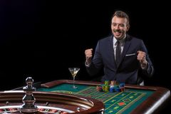 Gambler stakes playing at the roulette table. Risky entertainment of gambling stock photography