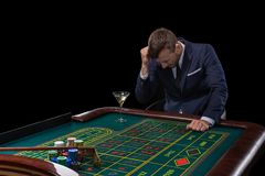 Gambler stakes playing at the roulette table. Risky entertainment of gambling royalty free stock photo