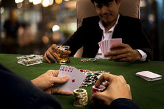 The gambler used psychology by adding bets for threatening rival. Close up to hand of the gambler show chance of winning and holding chips into the piles of bets Royalty Free Stock Photo