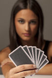 Gambler woman. Beautiful attractive girl holding poker cards and posing with a blank expression Royalty Free Stock Photography
