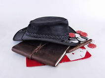 Gamblin Cowboy Gear. Vintage leather cowboy hat, leather covered diary, poker chips, aces, and a cigar on a red bandana cloth. On a white background Royalty Free Stock Photo