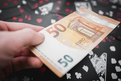 gambling 50 евро в руке над черной предпосылкой играя карточек стоковые фото