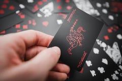 gambling Карточка шутника в руке над чернотой покрасила предпосылку играя карточек стоковая фотография