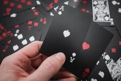 gambling 2 туза в руке в черноте покрасили предпосылку играя карточек стоковое изображение