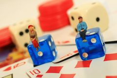 Gambling. Two mini people sit on dice with gambling environment royalty free stock image