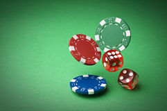 Gambling. Chips and dices on green background close up Royalty Free Stock Images