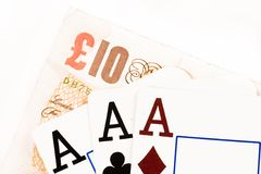 Gambling. 3 aces and a british 10 pound note on a white background Royalty Free Stock Photos