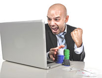Gambling addict businessman winning online poker with chips and cards on laptop Stock Image