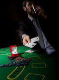 Gambling addiction. man in a business suit drinking brandy and throws cards with losing combination. casino chips Stock Photo