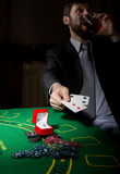 Gambling addiction. man in a business suit drinking brandy and throws cards with losing combination. casino chips Royalty Free Stock Image