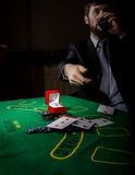 Gambling addiction. man in a business suit drinking brandy and throws cards with losing combination. casino chips Stock Photography
