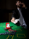 Gambling addiction. man in a business suit drinking brandy and throws cards with losing combination. casino chips Stock Image