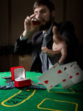 Gambling addiction. man in a business suit drinking brandy and throws cards with losing combination. casino chips Royalty Free Stock Photo