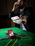 Gambling addiction. man in a business suit drinking brandy and throws cards with losing combination. casino chips Stock Photos