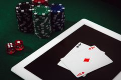 Gambling addiction on internet. Bet and win money playing poker online. Casino chips, cards and dices stacking on a laptop stock photos