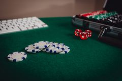 Playing poker online concept with a laptop on a green table with some chips. royalty free stock image