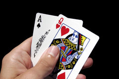 Gambling Cards In Hand. Left Hand Holding Gambling Cards - Ace Of Spades, Queen Of Hearts Royalty Free Stock Images