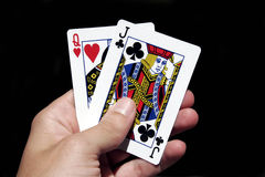 Gambling Cards In Hand. Left Hand Holding Gambling Cards - Ten Of Hearts And Black Jack royalty free stock image