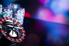 Gambling in casino. Casino theme background. High contrast image of casino roulette and poker chips on a gaming table, all on colorful bokeh background. Place Royalty Free Stock Photo