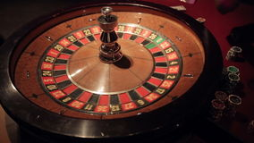 Gambling casino roulette spinning ball lands on number 11. Sequence stock video footage