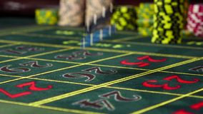 Gambling chips black, blue falling on roulette table, slow motion. Two gambling chips black and blue falling down on the standart roulette table with a lot of stock footage