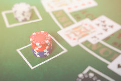 Gambling chips and cards on a green cloth Casino Stock Image