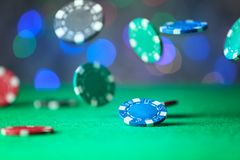 Gambling chips falling on green table. In casino royalty free stock image