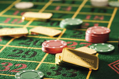 Gambling chips and gold bars on roulette table Stock Photography