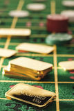 Gambling chips and gold bars on roulette table Stock Image