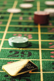 Gambling chips and gold bars on roulette table Royalty Free Stock Images