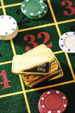 Gambling chips and gold bars on roulette table Royalty Free Stock Photos