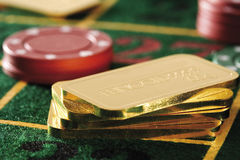 Gambling chips and gold bars on roulette table royalty free stock photo
