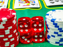 Gambling chips. Over green table cover with set of cards in the background royalty free stock photography