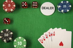 Gambling chips, red dice and card for poker on green felt background royalty free stock image