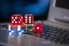 Gambling chips and red dice on laptop keyboard background Stock Photography