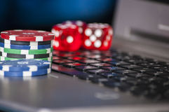 Gambling chips and red dice on laptop keyboard background Royalty Free Stock Photo