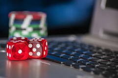 Gambling chips and red dice on laptop keyboard background Stock Photo