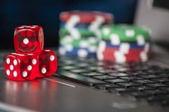 Gambling chips and red dice on laptop keyboard background Stock Photos